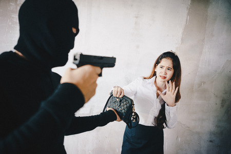 Thieves were threatened with a gun to office girl on the way she was walking home. Reklamní fotografie