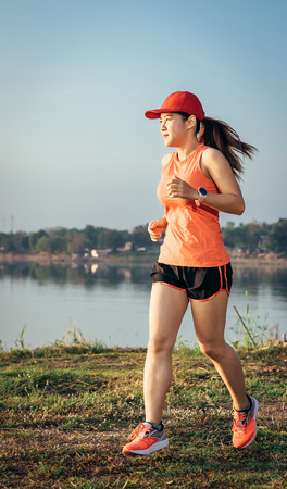 An asian woman athletic is jogging on the concrete road, she is warming her body and tideten her tying her shoes tightly fitting before workout. Stock Photo
