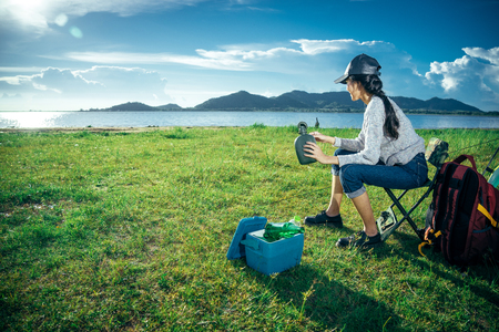 An Asian woman is sitting on the camping chair in front of the tent with red backpack. She is drinking some beer and looking the sunset on weekend holiday.Lifestyle and camping concept. Banco de Imagens