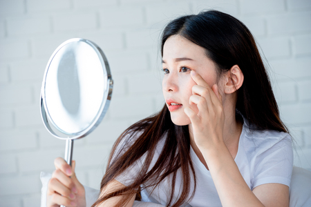Asian teenage woman  looking at mirror and squeeze acne problem on her face, skin care concept. Фото со стока