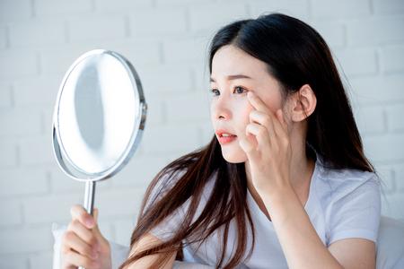 Aziatische tienervrouw die naar spiegel kijkt en acneprobleem op haar gezicht knijpt, huidverzorgingsconcept Stockfoto