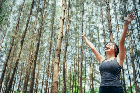 Asian girl is exercising and drinking cool water at the weekend in a pine forest green and lush beautiful. Sport girl and lifestyle concept.