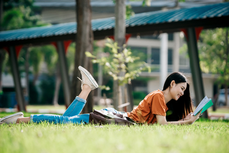 A young or teen asian girl student in university smiling and reading the book and look at the tablet or labtop computer in summer holiday. Stock Photo