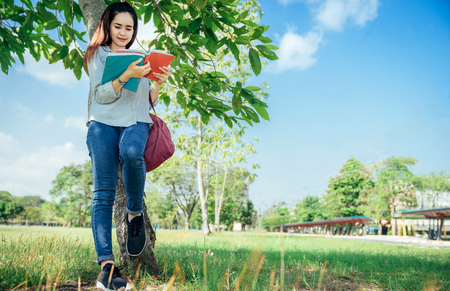 A group of teenage student in university smiling and reading the book in summer holiday.