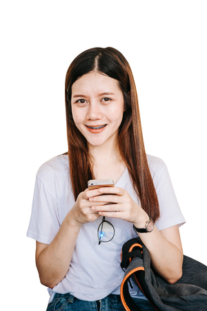 A young or teen Asian student in university smiling and reading the book and look at the mobile phone or laptop computer in summer holiday.