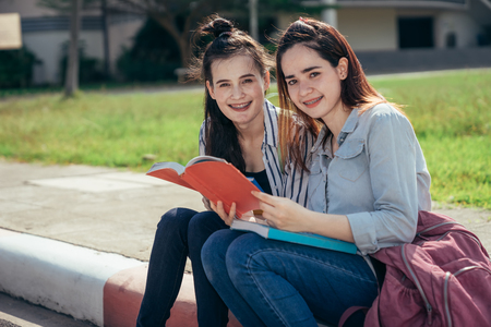 A group of teenage student in university smiling and reading the book in summer holiday, focus on second one. Stock Photo