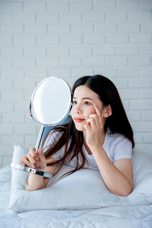 Asian teenage woman  looking at mirror and squeeze acne problem on her face, skin care concept. Archivio Fotografico