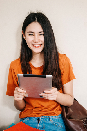 A young or teen Asian student in university smiling and reading the book and look at the tablet or laptop computer in summer holiday.
