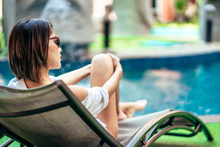 A beauty Asian woman enjoying with her summer vacation at swimming pool in Pattaya, Thailand.