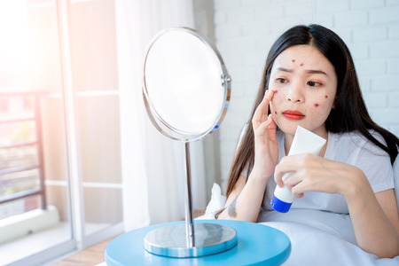 Asian teenage woman  looking at mirror and squeeze acne problem on her face, skin care concept. Zdjęcie Seryjne