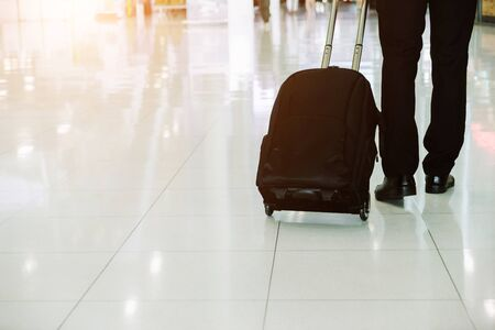 Elegant businessman checking e-mail on mobile phone while walking with suitcase inside airport, experienced male employer using cell telephone while waiting for taxi car coming before work travel Stockfoto