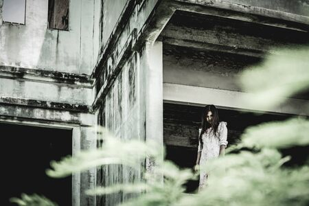 Zombie woman standing on the edge of the window in an abandoned building on Halloween. Women dressed in zombie