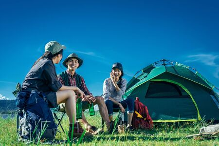 A  group of Asian friends sitting on chairs, drinking some beer and water together outside the tent near the fire while they has camping on Weekend holiday. Stock Photo