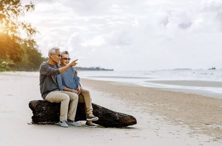 Asian senior couple or elderly people walking and siting at the beach on their weekend vacation holiday. Retirement vaction concept. Stok Fotoğraf