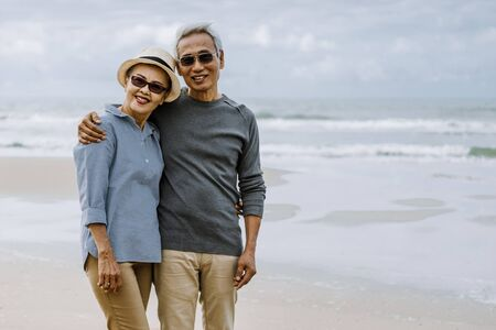 Asian senior couple or elderly people walking and siting at the beach on their weekend vacation holiday. Retirement vaction concept. Stock Photo