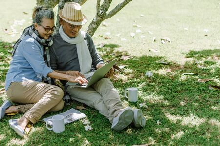Asian senior couple or elderly people siting at garden and using laptop to online web site email or shopping. Retirement vaction concept.