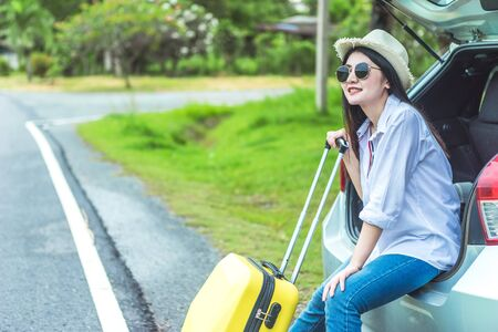 Asian woman holding a wheel suitcase bag and sitting on a car door rim in vacation holiday with car travel roadtrip. Car travel concept.