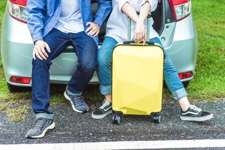 Happy Asian couple traveling and sitting in a car open trunk and wtch sunrise. Car travel concept. Banque d'images - 131855421