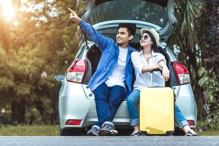 Happy Asian couple traveling and sitting in a car open trunk and wtch sunrise. Car travel concept.