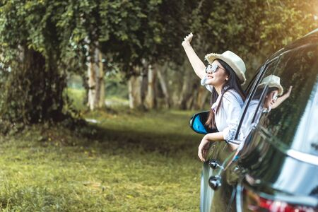 Happy Asian young woman enjoying a ride in a car with hand greeting. The concept of road travel and adventure. Banque d'images - 131855697
