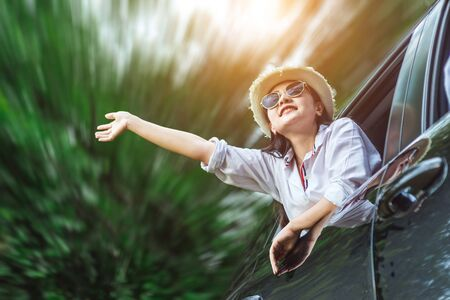 Happy Asian young woman enjoying a ride in a car with hand greeting. The concept of road travel and adventure.