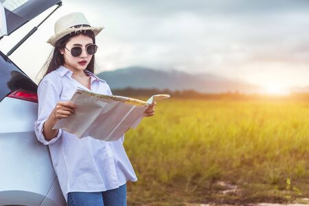 Asian woman looking a map in vacation holiday with car travel roadtrip. Car travel concept. Banque d'images - 131855403