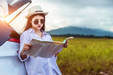 Asian woman looking a map in vacation holiday with car travel roadtrip. Car travel concept. Stock fotó