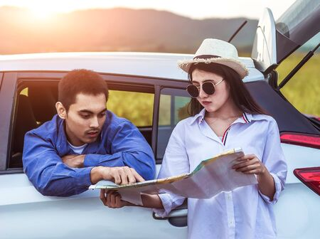Happy young Asian friend looking to the map traveling by the eco car on vacation holiday with travel road trip. Car travel concept. Stock fotó