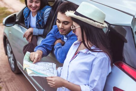Happy young Asian friend looking to the map traveling by the eco car on vacation holiday with travel road trip. Main focust is a man. Car travel concept. Banque d'images - 131855318