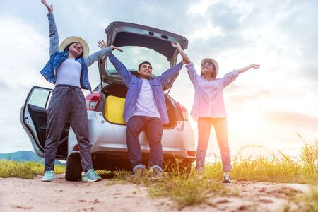 Happy young Asian friend sitting and standing behind the car on vacation holiday with travel road trip. Car travel concept.
