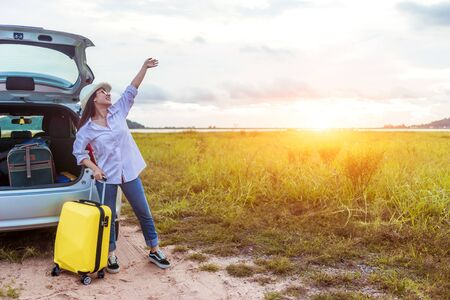 Asian woman sitting on car roof and holding the suitcase bag in vacation holiday with car travel roadtrip. Car travel concept.