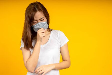 Asian woman is coughing or sneezing wearing hygienic mask to protect virus, COVID 19 or Colona Virus infection and dust PM 2.5 pollution isolate on yellow background