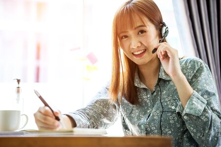 Young femal Asain using laptop to work from home and communication online internet with customer in home. Cozy office workplace, remote work or call center. E-Learning concept. Stockfoto