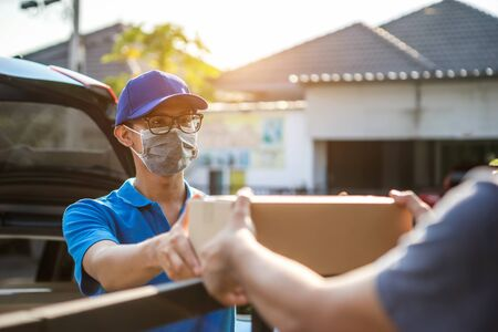 Asian delivery man wearing mask delivers parcel, customer in medical gloves signs on tablet. Delivery service under quarantine, disease outbreak, coronavirus covid-19 pandemic conditions.