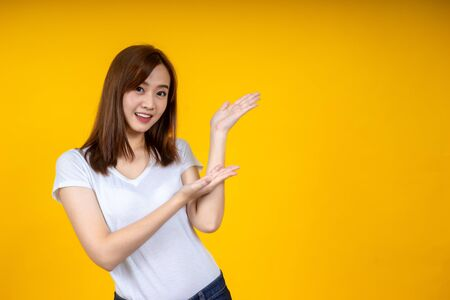Young elegant Asian woman smiling and pointing to empty copy space isolated on yellow background Stockfoto