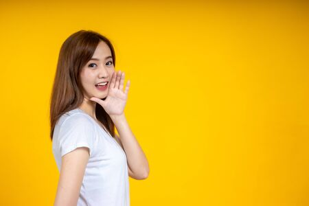 Young Asian beautiful woman wearing white t-shirt over yellow isolated background hand on mouth telling secret rumor, whispering malicious talk conversation Stockfoto