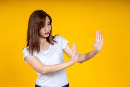 Young Asian woman showing stop sign, don't come closer gesture. Focused on hand. Emotions, body language concept. Social Distance concept.