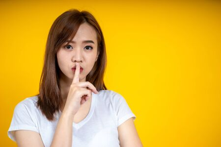 Young Asain woman requires silence. Young beautiful brunette has put forefinger to lips as sign of silence, isolated on yellow Stockfoto