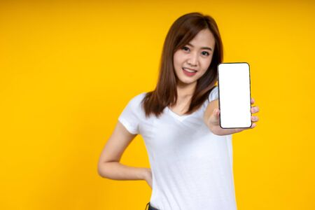 Smiling young Asian woman is showing a smartphone standing on yellow background.