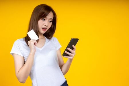 Asian women are holding credit cards and are excited about the promotion of online products on mobile. Yellow isolated background portrait