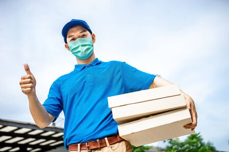 Asian delivery man in blue t-shirt carrying pizza box and showing thumb up. Delivery man concept.