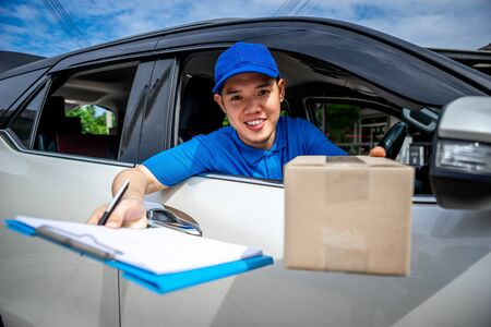 Asian delivery man in blue t-shirt on car send the box and document to sign. Delivery man concept. Stockfoto