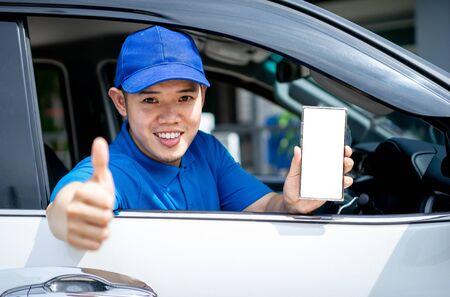 Asian delivery man in blue t-shirt on car showing thumb up and application on mobile. Delivery man concept.