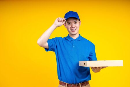 Young Asian handsome delivery man holding a pizza box on hand and touching his cap over yellow isolate background. Work from home and delivery concept.