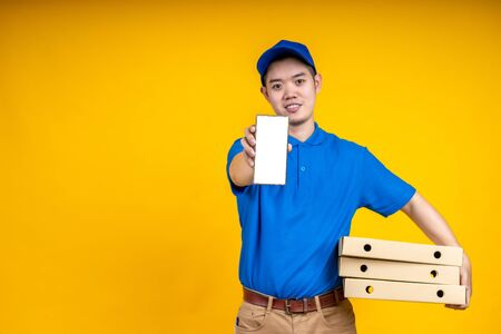 Young Asian handsome delivery man holding box on left arm and showing application on mobile over yellow isolate background. Work from home and delivery concept.