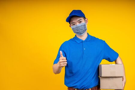 Young Asian handsome delivery man wearing mask holding box left arm thumb up over yellow isolate background. Work from home and delivery concept. Stockfoto