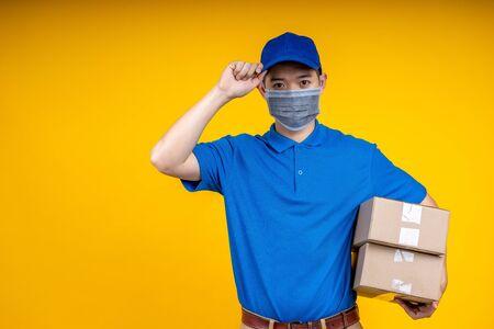 Junger asiatischer gutaussehender Liefermann, der eine Maske trägt, die Kisten auf dem linken Arm hält und seine Mütze über gelbem isolierendem Hintergrund berührt. Arbeit von zu Hause aus und Lieferkonzept.