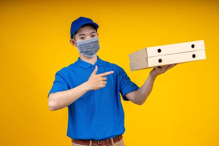 Young Asian handsome delivery man wearing mask pointing to pizza boxs over yellow isolate background. Work from home and delivery concept.