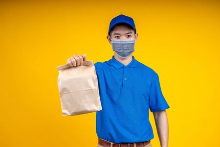 Young Asian handsome delivery man wearing mark holding a food paper bag on right hand over yellow isolate background. Work from home and delivery concept.