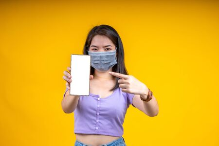 Young Asian woman wearing mask points at Smartphone over yellow background. Corona virus or covid-19 concept. Stockfoto